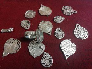 Pezas en prata preparadas para rematar: figa, petróglifo e aneis